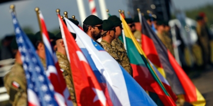 "Participants hold flags of their countries during the ""Noble Sword-14"" NATO international tactical exercise at the land forces training centre in Oleszno"