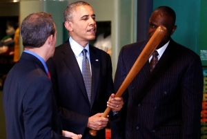 U.S. President Barack Obama holds a Babe Ruth bat as he tours the National Baseball Hall of Fame with Hall of Fame President Jeff Idelson (L) and former player Andre Dawson (R), in Cooperstown, New York, May 22, 2014. Obama is highlighting the tourism industry during his visit to the museum. Robinson was the first African American player in Major League Baseball. REUTERS/Jonathan Ernst (UNITED STATES - Tags: POLITICS SPORT BASEBALL)