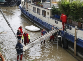 Firefighters install a footbridge to access a barge on the river Seine after its banks became flooded following heavy rainfalls on June 1, 2016 in Paris. Torrential downpours have lashed parts of northern Europe in recent days, leaving four dead in Germany, breaching the banks of the Seine in Paris and flooding rural roads and villages. / AFP PHOTO / FRANCOIS GUILLOT
