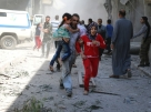 A Syrian family runs for cover amid the rubble of destroyed buildings following a reported air strike on the rebel-held neighbourhood of Al-Qatarji in the northern Syrian city of Aleppo, on April 29, 2016. Fresh bombardment shook Syria's second city Aleppo, severely damaging a local clinic as outrage grows over an earlier air strike that destroyed a hospital. The northern city has been battered by a week of air strikes, rocket fire, and shelling, leaving more than 200 civilians dead across the metropolis. The renewed violence has all but collapsed a fragile ceasefire deal that had brought an unprecedented lull in fighting since February 27. / AFP PHOTO / AMEER ALHALBI
