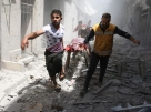 Syrian men carry a body on a stretcher amid the rubble of destroyed buildings following a reported air strike on the rebel-held neighbourhood of Al-Qatarji in the northern Syrian city of Aleppo, on April 29, 2016. Fresh bombardment shook Syria's second city Aleppo, severely damaging a local clinic as outrage grows over an earlier air strike that destroyed a hospital. The northern city has been battered by a week of air strikes, rocket fire, and shelling, leaving more than 200 civilians dead across the metropolis. The renewed violence has all but collapsed a fragile ceasefire deal that had brought an unprecedented lull in fighting since February 27. / AFP PHOTO / AMEER ALHALBI